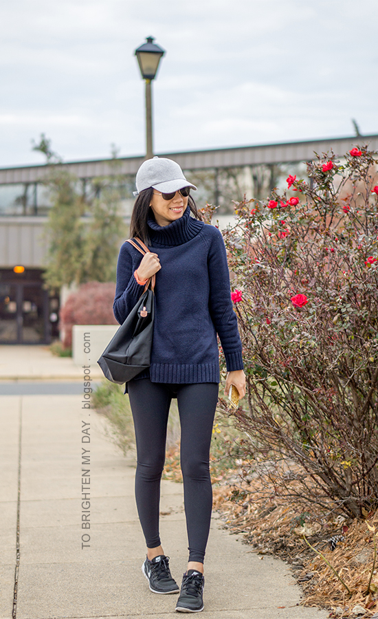 gray baseball cap, navy blue turtleneck sweater tunic, black leggings, black tote, black sneakers