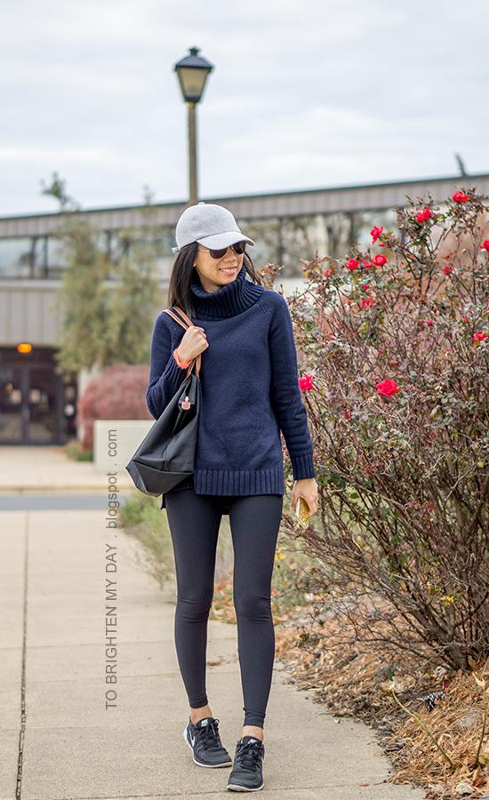 gray baseball cap, navy blue turtleneck sweater tunic, black leggings, black tote, black sneakers