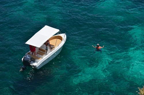 Ein kleines Boot mit Sonnendach und einem Schwimmer im Wasser.