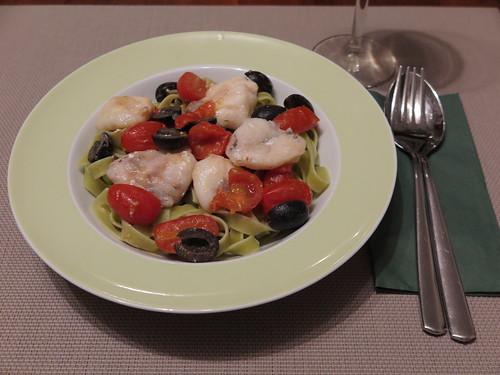 Seeteufelbäckchen in einer Soße mit Oliven und Tomaten auf Bandnudeln