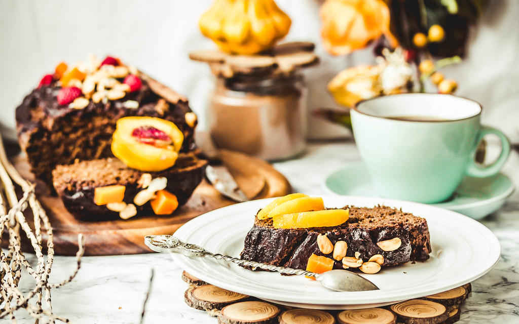 piece of chocolate cake with pumpkin, nuts and fresh peaches on a white plate