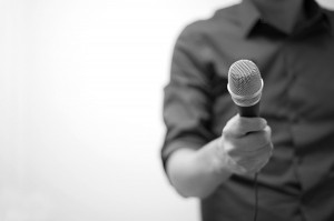 Picture of a man holding out a microphone.