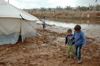 Children walk near flooding in tented settlement, Jordan | by Oxfam International