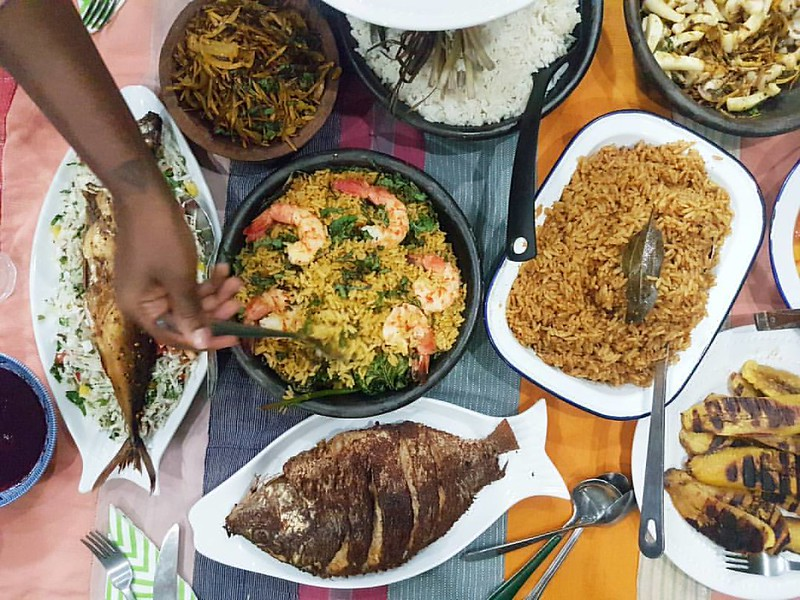 In this view: {About last night with @azemezi @yagazieemezi @theforgetterseye} Lemon grass white rice Banga Jollof with scent leaf & seafood Groundnut Jollof Ugba salad, plain and with squid Plantain, grilled and fried Fried tilapia Salad - cassava