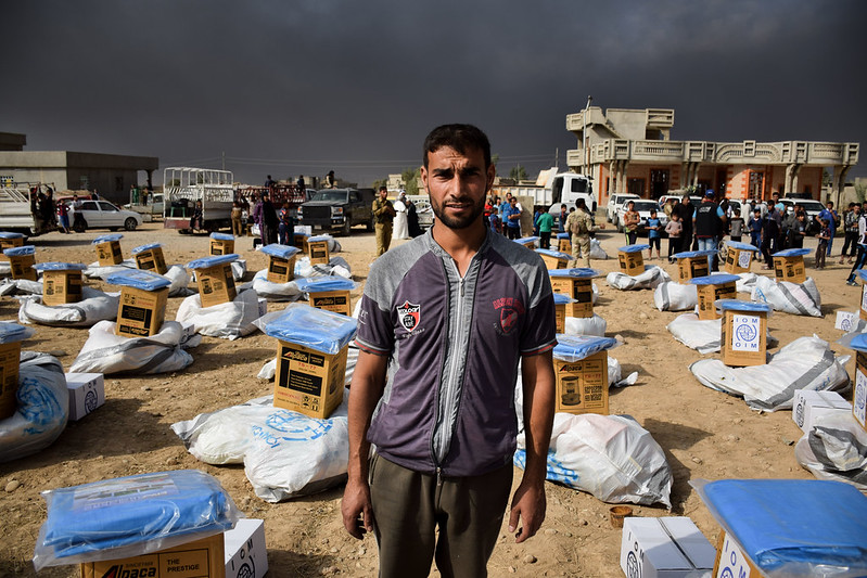 A man stands amidst relief kits being distributed by IOM for people displaced from Mosul, Iraq
