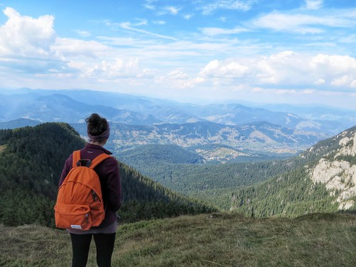 Looking out across the view from Ceahlău Massif with an orange Eastpak backpack | by Flora_AB