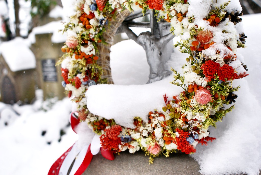 Couronne de fleurs séchées sous la neige dans le cimetière de Zakopane.