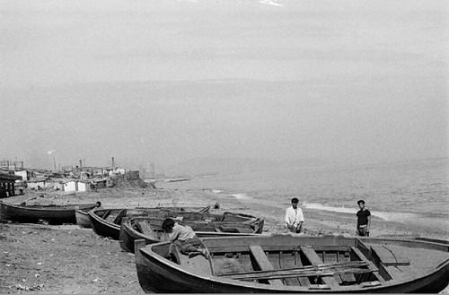 Plage de Barcelone avec des bateaux de pêche au premier plan et le bidonville au deuxième.