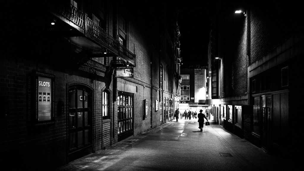 A man walking at night london england black and white street photography