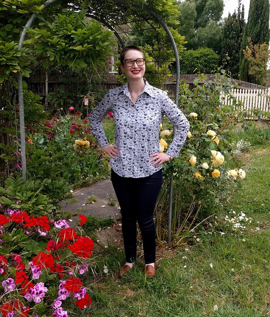 A woman stands in a garden archway. She wears a cutlery-print button-up shirt and dark skinny jeans.