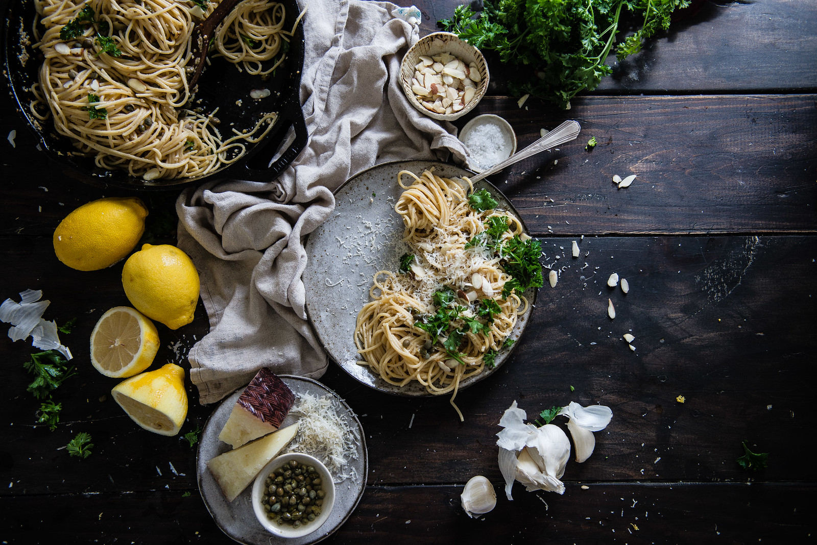 garlicky spaghetti with lemon, capers, & almonds | two red bowls