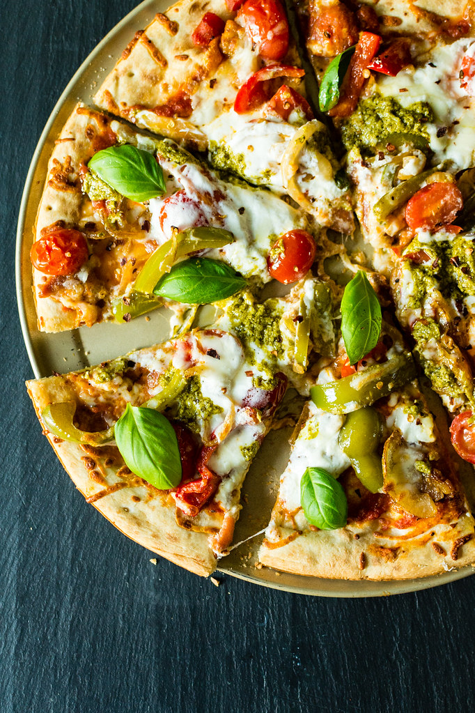 Grilled Bacon Pesto Pizza with fresh Burrata - Who doesn't love grilled pizza? This is a quick and easy recipe that's so delicious you'll need to make two! See the recipe at GirlCarnivore.com