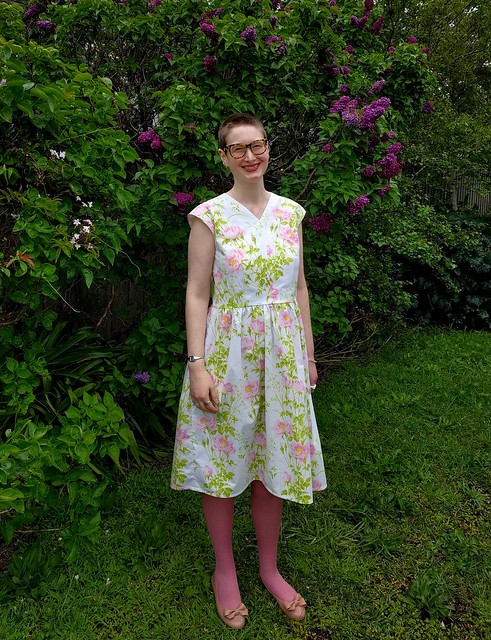 A woman poses in a garden, wearing a 50s style frock in a floral print