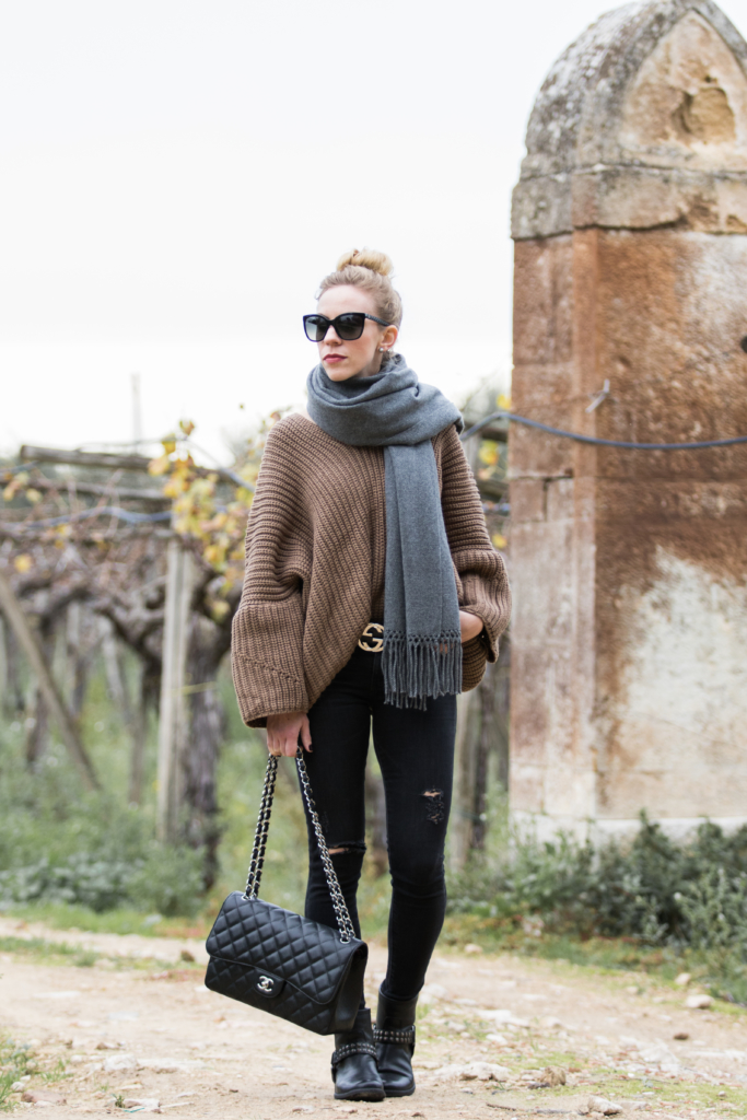 casual-travel-outfit-with-oversized-sweater-and-distressed-black-jeans-Chanel-Jumbo-flap-bag-black-with-silver-hardware