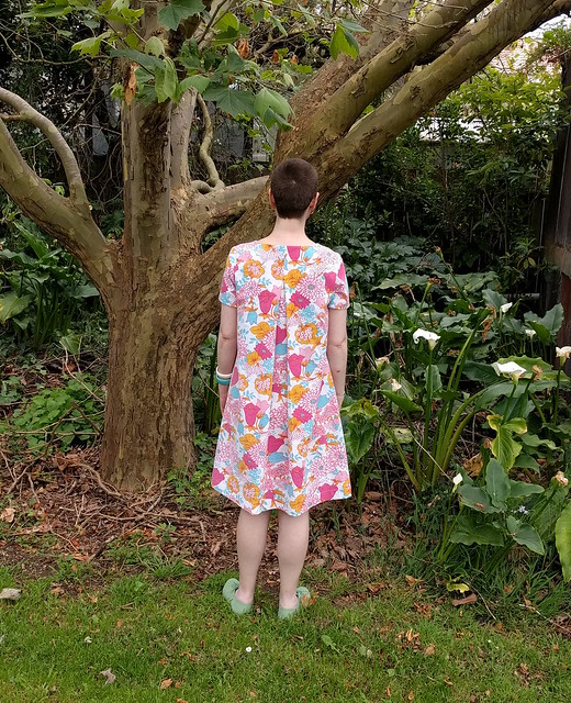 A woman poses in a garden in a retro floral print shift dress, Burda short a-line dress 03/2016 #106