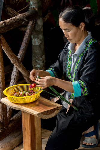 Hmong woman making flowers to sell
