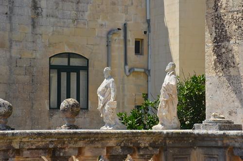 Zwei Statuen in einem Garten an der Stadtmauer.