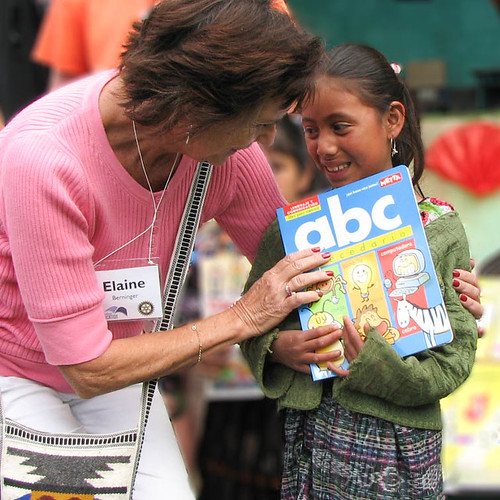 Elaine gives a book to a little girl
