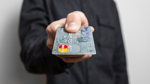 Holding credit card | by cafecredit