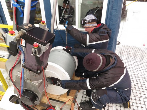 Putting the winch back together after diagnosing a short in the winch cable. From left to right is Zack Meulemans (inside the control room), Jay Johnson and Shawntel Stapleton. | by U.S. Ice Drilling