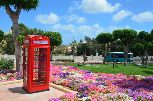 Am Busparkplatz von Victoria steht eine rote Telefonzelle vor Blumen und englischem Rasen