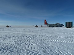 An LC-130 is being unloaded while a pallet of ice cores waits to be loaded at the lef