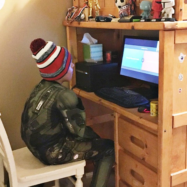 Master Chief wearing costume, wearing a stocking cap, watching videos on the computer. #owenchristopher 😂