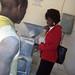 Rebecca Mwanza inspects a hammer-mill. Credit: Lewis Mwanangombe/IPS