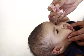 A child receives an oral vaccine | by World Bank Photo Collection
