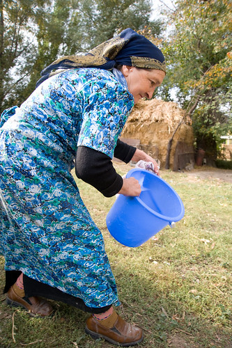 Galima Muhametarimovna cleans a bucket before milking one of her four cows in her yard | by UN Women Gallery