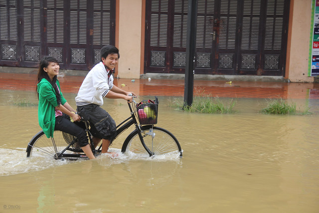 Boy and girl riding a bike through the flooded streets of Hoi An, Vietnam