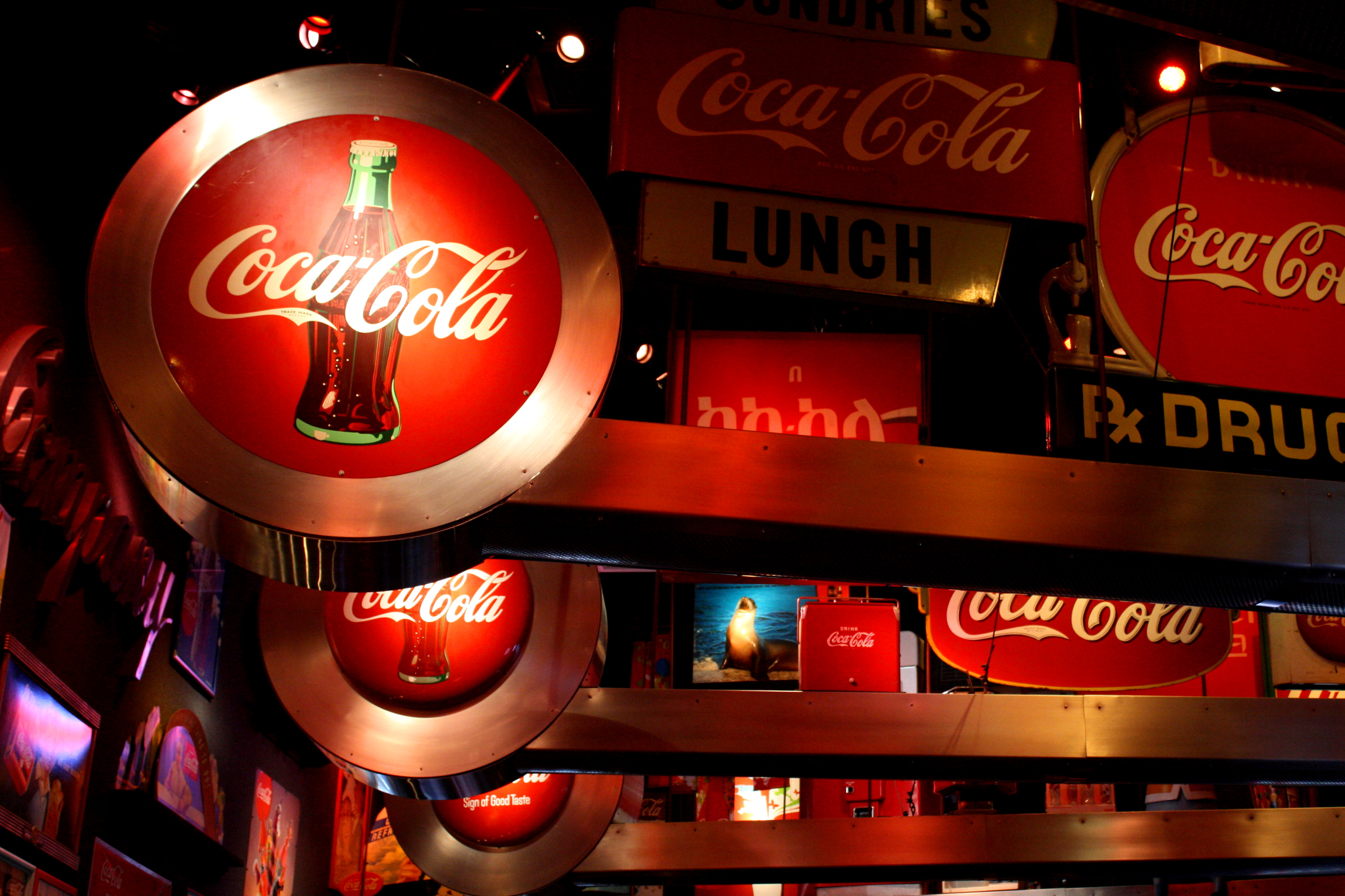 Image of multiple lighted Coca Cola Signs, dominant colors are red, white, and black