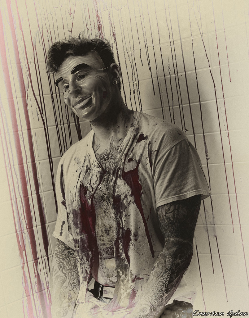 Tattooed Man Sits In A Blood Splattered Room Wearing Creepy Mask