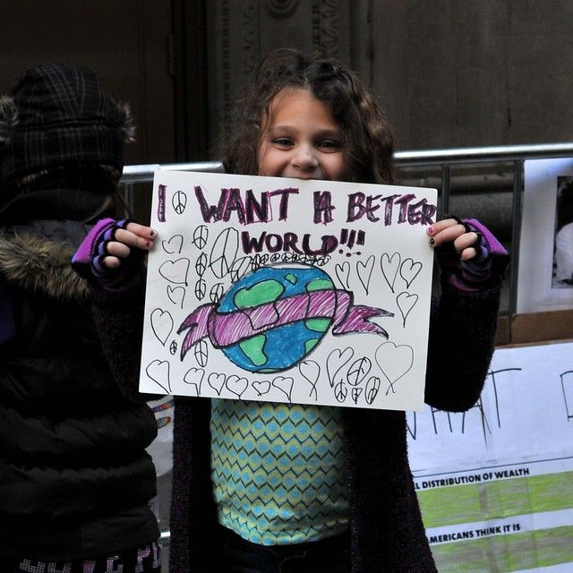 little girl holding a sign saying I want a better world