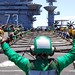 GA native/Sailor signals for Sailors to set up the aircraft barricade during a drill aboard USS George Washington