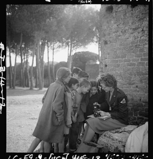 [Toni Frissell, sitting, holding camera on her lap, with several children standing around her, somewhere in Europe] (LOC) | by The Library of Congress