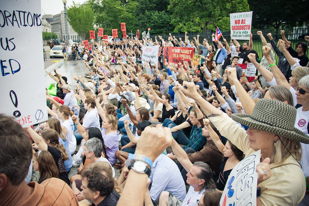 Climate organizers raise their fists in direct action at the White House