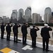 Members of the Fire Department of the City of New York present honors as they pass the World Trade Center and the National September 11 Memorial aboard USS New York