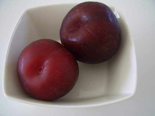 Two plums in glass bowl