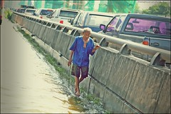 An old man walking beside a motor way to avoid flooded water