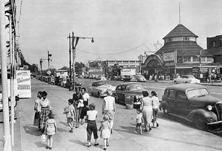 Moms with kids stroll, 1940s and older cars, Schlitz beer truck makes a delivery. Surf Ave looking east at West 6th St to Stubbmann's Pavilion and amusement park. Brooklyn, New York. 1953 | by wavz13