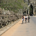 Cyclists passing row of statues, south gate of Angkor Thom
