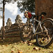 Bike leaning on a tree beside some ruins at Angkor Wat