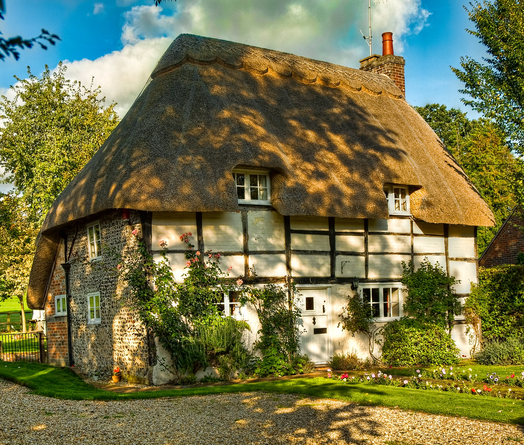 Dappled Sunlight On A Pretty Thatched Cottage At Stoke In