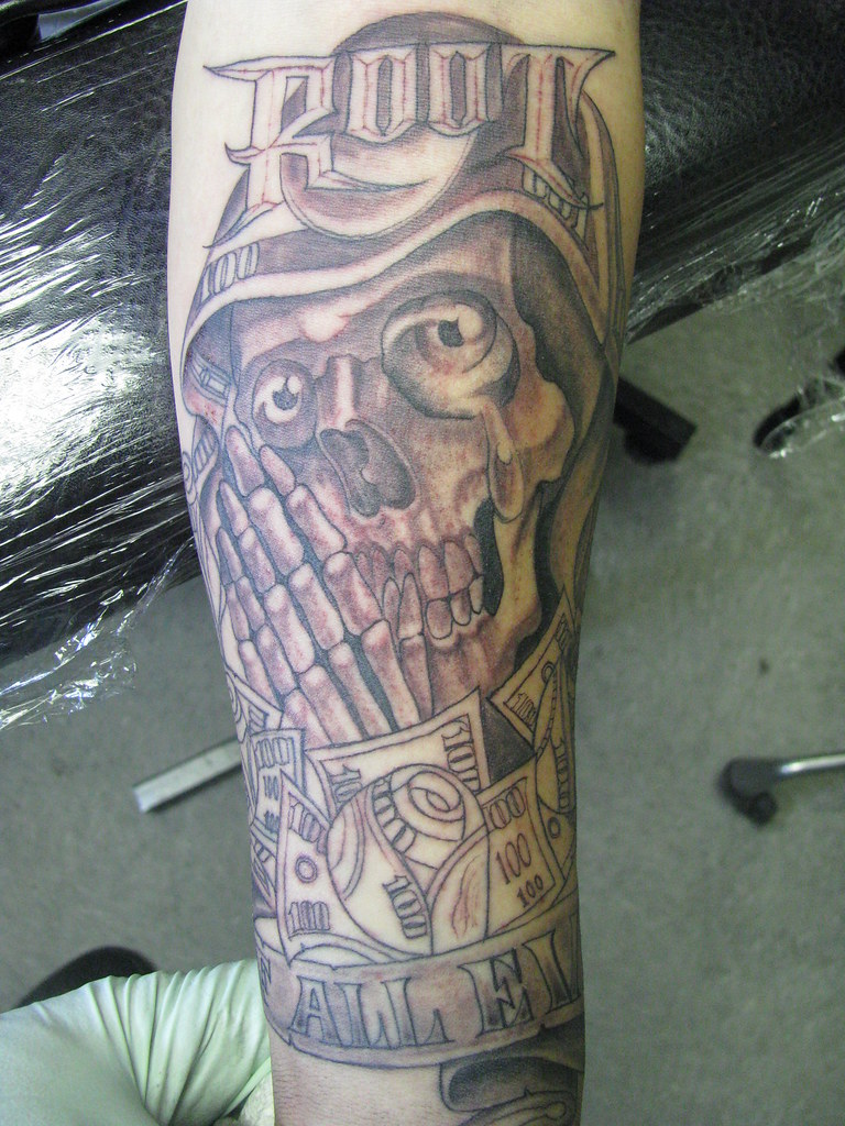 Root Of All Evil Tattoo Of Skeleton Praying On Sleeve