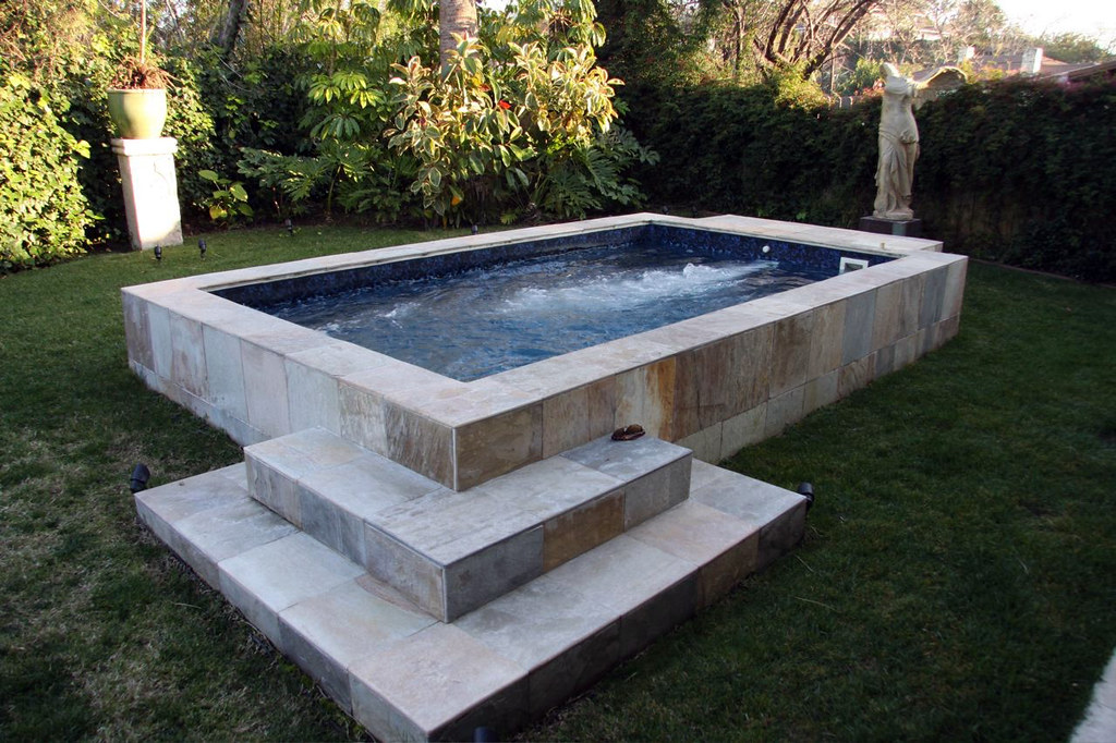 Medallion pools ultra swim spa outdoor with marble surroun for Spa swimming pool