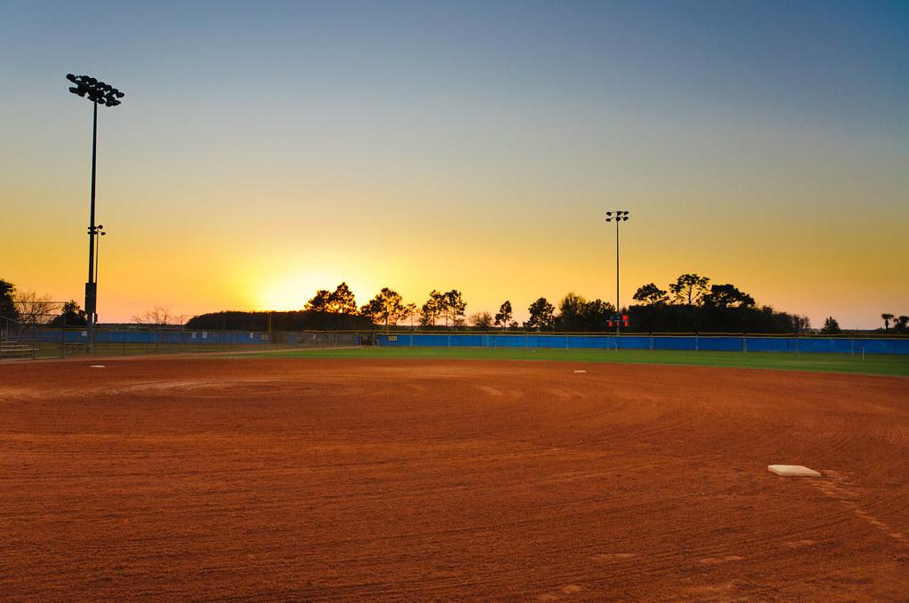 Baseball Field at Sunset | The setting sun casts a warm ...