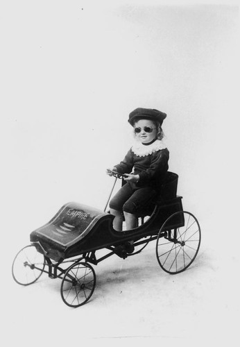 Child driving a toy car | by State Library of Queensland, Australia