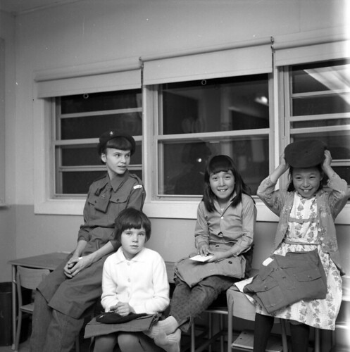 Girl Guides and Brownies sitting on a table / Guides et Brownies assises sur une table | by BiblioArchives / LibraryArchives