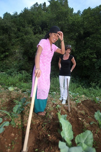 The delegate helps a local woman turn over some agricultural land | by Plan Asia